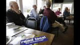 """In this Wednesday, April 10, 2019 photo Lanny Lambert, of Pittsfield, Mass., left, listens listens during a """"coffee with the president of The Berkshire Eagle"""" gathering, in Williamstown, Mass. The paper now features a new 12-page lifestyle section for Sunday editions, a reconstituted editorial board, a new monthly magazine, and the newspaper print edition is wider. That level of expansion is stunning in an era where U.S. newspaper newsroom employment has shrunk by nearly half over the past 15 years. (AP Photo/Steven Senne)"""