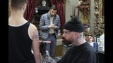 In this Thursday, April 11, 2019 photo Berkshire Eagle writer Benjamin Cassidy, behind center, takes notes as tattoo artist Brian Brown, of Dalton, Mass., right, creates an image on the arm and shoulder of customer Scott Forrest, of North Adams, Mass., left, at a tattoo parlor in Dalton, Mass. The paper now features a new 12-page lifestyle section for Sunday editions, a reconstituted editorial board, a new monthly magazine, and the newspaper print edition is wider. That level of expansion is stunning in an era where U.S. newspaper newsroom employment has shrunk by nearly half over the past 15 years. (AP Photo/Steven Senne)