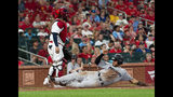 Miami Marlins' Harold Ramirez slides safely into home next to St. Louis Cardinals catcher Yadier Molina during the eighth inning of a baseball game Tuesday, June 18, 2019, in St. Louis. (AP Photo/L.G. Patterson)