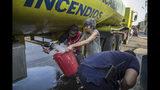 En la imagen, tomada el 14 de mayo de 2019, una mujer llena un cubo de agua potable en un camión cisterna durante los cortes de agua provocados por la falta de electricidad, en Maracaibo, Venezuela. La oposición culpa de la miseria en Venezuela a las erróneas políticas económicas y a la mala gestión y la corrupción del gobierno socialista instaurado por el fallecido Hugo Chávez. (AP Foto/Rodrigo Abd)