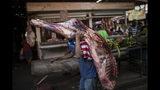 En la imagen, tomada el 16 de mayo de 2019, un vendedor carga con una pieza de carne en una carnicería en un mercado de Maracaibo, Venezuela. Tendrá que venderla pronto ya que, sin refrigeración, los alimentos perecederos se estropean rápidamente en las asfixiantes temperaturas de Maracaibo. (AP Foto/Rodrigo Abd)