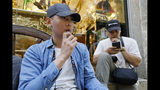 In this Monday, June 17, 2019, photo, Joshua Ni, 24, and Fritz Ramirez, 23, vape from electronic cigarettes in San Francisco. San Francisco supervisors are considering whether to move the city toward becoming the first in the United States to ban all sales of electronic cigarettes in an effort to crack down on youth vaping. The plan would ban the sale and distribution of e-cigarettes, as well as prohibit e-cigarette manufacturing on city property. (AP Photo/Samantha Maldonado)