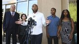 Rev. Jarrett Maupin, center, a civil rights advocate, speaks during a news conference as Dravon Ames, second from right, and Iesha Harper, right, are joined by their attorneys Sandra Slaton, second from left, and Tom Horne, left, at Phoenix City Hall, Monday, June 17, 2019, in Phoenix. Ames and his pregnant fiancée, Harper, who had guns aimed at them by Phoenix police during a response to a shoplifting report say they don't accept the apologies of the city's police chief and mayor and want the officers involved to be fired. (AP Photo/Ross D. Franklin)