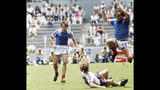 """FILE - In this file photo dated June 25, 1986, France's Michel Platini, right, jumps over Germany's Ditmar Jakobs during the Football World Cup Semi-Final in Guadalajara, Mexico, with French defender Luis Fernandez, left. Affectionately nicknamed """"Le Roi"""" (The King), Michel Platini bestrode the soccer field with inimitable elegance as the world's best player of the early 1980s, but his lofty reputation seems to have been tainted. (AP Photo/Blaha, FILE)"""