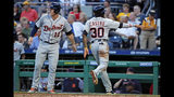Los jugadores de los Tigres de Detroit, el venezolano Harold Castro (30) y Brandon Dixon (12), anotan en un error cargado al tercera base de los Piratas de Pittsburgh, Jung Ho Kang, en el cuarto inning de un juego de béisbol en Pittsburgh, el martes 18 de junio de 2019. (AP Foto/Gene J. Puskar)