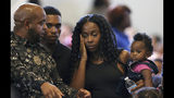 Rev. Jarrett Maupin, left, arrives with Dravon Ames, second from left, Iesha Harper, second from right, and one of the family's two daughters, 1-year-old London, prior to the start of a community meeting, Tuesday, June 18, 2019, in Phoenix. The community meeting stems from reaction to a videotaped encounter that surfaced recently of Ames and his pregnant fiancee, Harper, having had guns aimed at them by Phoenix police during a response to a shoplifting report, as well as the issue of recent police-involved shootings in the community. (AP Photo/Ross D. Franklin)