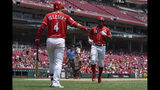 Cincinnati Reds' Yasiel Puig celebrates hitting a solo home run with Jose Iglesias in the second inning of a baseball game against the Houston Astros, Wednesday, June 19, 2019, in Cincinnati. (AP Photo/Aaron Doster)