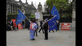 Anti-Brexit remain supporters stand with European flags and pro-Brexit leave supporters hold red placards as they all protest outside the Houses of Parliament in London, Wednesday, June 19, 2019. Britain's Conservative Party are set to kick one more candidate out of the contest to become the country's next prime minister, as rivals scramble to catch front-runner Boris Johnson. The five-strong field will be narrowed in elimination votes by Tory lawmakers Wednesday and Thursday, with the two top candidates going to a runoff of party members across the country. (AP Photo/Matt Dunham)