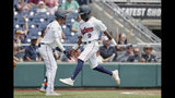 Auburn's Ryan Bliss (9) is greeted by Auburn's Will Holland, left, after he scored a run against Louisville on a double by Conor Davis in the seventh inning of an NCAA College World Series baseball game in Omaha, Neb., Wednesday, June 19, 2019. (AP Photo/Nati Harnik)