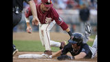 Texas Tech's Gabe Holt, right, survives a pickoff attempt by Florida State first baseman Cal Raleigh during the fifth inning of an NCAA College World Series baseball game in Omaha, Neb., Wednesday, June 19, 2019. (AP Photo/Nati Harnik)