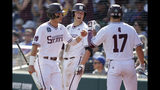 Mississippi State's Jake Mangum, left, is greeted by teammates, including Justin Foscue (17), after he scored against Vanderbilt on a double by Tanner Allen during the seventh inning of an NCAA College World Series baseball game in Omaha, Neb., Wednesday, June 19, 2019. (AP Photo/Nati Harnik)
