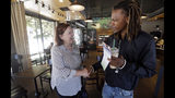 In this photo taken Monday, June 10, 2019, Seattle City Council candidate Pat Murakami, left, greets voter James Williams at a coffee shop in Seattle. A first-of-its-kind public campaign finance program in Seattle gives voters vouchers worth $100 to pass on to any candidate they want. Now in its second election cycle, advocates say the program can level the political playing field, although its first round in Seattle showed mixed results. (AP Photo/Elaine Thompson)