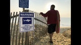 FILE - In this Aug. 16, 2018, file photo, Steve McFadden, of Plattsburgh, N.Y., gazes at Long Nook Beach in Truro, Mass. Researchers on Cape Cod are launching a new study focused on the hunting and feeding habits of the region's great white sharks following two attacks on humans in 2018, including the state's first fatal one in more than 80 years. (AP Photo/William J. Kole, File)