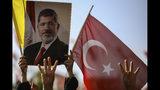 Gente alzando un cartel con la imagen del expresidente de Egipto Mohammed Morsi, antes de un servicio funerario en ausencia por el exmandatario, en la mezquita Fatih en Estambul, el martes 18 de junio de 2019. El presidente de Turquía, Recep Tayyip Erdogan, que tenía estrechos lazos con Morsi, asistió al funeral. (AP Foto/Emrah Gurel)