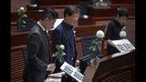 Legisladores prodemocracia rinden homenaje en silencio a un hombre que murió tras caerse el sábado cuando colgaba una pancarta de un andamio durante una protesta, en el Consejo Legislativo de Hong Kong, el miércoles 19 de junio de 2019. (AP Foto/Vincent Yu)