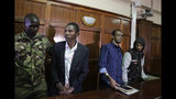 From left to right, defendants Rashid Charles Mberesero, Hassan Aden Hassan and Mohamed Abdi Abikar, are led from the dock by a police officer, left, after their verdict at a court in Nairobi, Kenya Wednesday, June 19, 2019. The Kenyan court found Mberesero, Hassan and Abikar guilty of conspiracy to commit a terror attack after phone records and handwriting linked them to the 2015 Garissa University assault that killed 148 people, while a fourth person, Sahal Diriye Hussein, was acquitted. (AP Photo/Khalil Senosi)