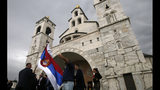 "In this Saturday, Oct. 15, 2016 file photo, a man holds Serbian flag during a wedding ceremony in front of the Serbian Orthodox Church of Christ's Resurrection in Podgorica, Montenegro. A Serb official has branded Montenegro a ""criminal"" state and threatened a ""fierce"" response over the neighboring country's plans to introduce a church law. The draft law calls for all religious communities in Montenegro to provide proof that they owned their property before 1918 when the small Adriatic state lost its independence and became part of the Serb-dominated Kingdom of Serbs, Croats and Slovenes. If they don't, the property becomes state owned. (AP Photo/Darko Vojinovic, File)"