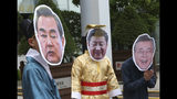 """South Korean protesters wear a mask of Chinese President Xi Jinping, center, Foreign Minister Wang Yi, left, and South Korean President Moon Jae-in, right, during a rally to denounce South Korean government's policy on China near the Chinese Embassy in Seoul, South Korea, Wednesday, June 19, 2019. Chinese President Xi praised North Korea for moving in the """"right direction"""" by politically resolving issues on the Korean Peninsula in an essay published in both countries' official media Wednesday on the eve of Xi's visit to Pyongyang to meet North Korean leader Kim Jong Un. (AP Photo/Ahn Young-joon)"""