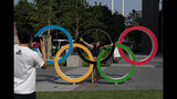 In this June 19, 2019, photo, photo, Tokyo residents Yuuma Sakai, foreground, takes photos of his wife, Hiroyo, with the Olympic rings set up near New National Stadium in Tokyo. Millions were going to be disappointed starting Thursday when applicants in a ticket lottery, for Japan residents, only, began learning if they landed tickets. The same will be true for residents outside Japan who could experience a similar dejection: too much demand and too few tickets. (AP Photo/Jae C. Hong)