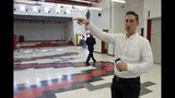 This June 14, 2019, photo shows Jeremy Price, a deputy chief of staff to Alaska Gov. Mike Dunleavy, showing reporters the cafeteria at Wasilla Middle School in Wasilla, Alaska, that would be available to lawmakers. Dunleavy has called lawmakers into special session in Wasilla beginning July 8, but some lawmakers have expressed concerns over security and logistics with the location more than 500 miles from the state capital of Juneau, Alaska. (AP Photo/Mark Thiessen)