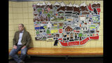 This June 14, 2019, photo shows Jeff Turner, the deputy communications director for Alaska Gov. Mike Dunleavy, sitting next to artwork displayed at Wasilla Middle School in Wasilla, Alaska. Dunleavy has called lawmakers into special session in Wasilla beginning July 8, but some lawmakers have expressed concerns over security and logistics with the location more than 500 miles from the state capital of Juneau, Alaska. (AP Photo/Mark Thiessen)