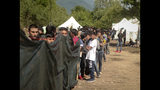 In this photo taken on Wednesday, June 19, 2019, migrants and refugees wait in line to receive supplies from the Red Cross at the Vucijak camp outside Bihac, Bosnia. Still deeply scarred by a brutal inter-ethnic war in the 1990s, Bosnia has become the chief bottleneck in the main land route for thousands of migrants seeking a better life in Europe. According to Bosnian government statistics, 34,000 newcomers crossed into the country since the beginning of 2018, including 9,000 who arrived in the first five months of this year. (AP Photo/Almir Alic)