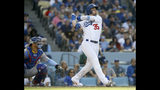 Los Angeles Dodgers' Cody Bellinger, right, watches his solo home run with Chicago Cubs catcher Willson Contreras, left, during the sixth inning of a baseball game in Los Angeles, Sunday, June 16, 2019. (AP Photo/Alex Gallardo)