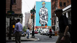 In this Tuesday, June 18, 2019 photo, pedestrians walk near a Mural Arts Philadelphia mural of Najee Spencer-Young by artist Amy Sherald by in Philadelphia. Sherald is the artist who painted the official portrait of Michelle Obama. (AP Photo/Matt Rourke)