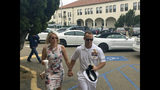 Navy Special Operations Chief Edward Gallagher, right, walks with his wife, Andrea Gallagher, as they arrive to military court on Naval Base San Diego, Thursday, June 20, 2019, in San Diego. More former SEALs were expected to testify on Thursday in the case against Gallagher, who has pleaded not guilty to murder and attempted murder stemming from his 2017 tour of duty in Iraq. (AP Photo/Julie Watson)