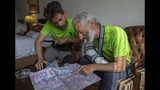 The team leader, Tarcisio Bellò, 57, right, shows the site of avalanche to his team member Luca Morellato in Islamabad, Pakistan, Thursday, June 20, 2019. The renowned Italian mountaineer, who narrowly survived along-with six other members of an expedition on a mountain, burst into tears Thursday when he recalled how helplessly he saw one of his Pakistani colleagues being swept away by an avalanche that struck them at an altitude of around 5,300 meters (17,390 feet) earlier this week. (AP Photo/B.K. Bangash)