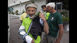 The team leader, Tarcisio Bellò, 57, points at a traditional Pakistani cap he wears while leaving fo Italian embassy in Islamabad, Pakistan, Thursday, June 20, 2019. The renowned Italian mountaineer, who narrowly survived along-with six other members of an expedition on a mountain, burst into tears Thursday when he recalled how helplessly he saw one of his Pakistani colleagues being swept away by an avalanche that struck them at an altitude of around 5,300 meters (17,390 feet) earlier this week. (AP Photo/B.K. Bangash)