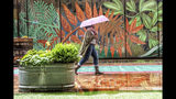 A woman shields from the rain with an umbrella as she walks near 5th and Market street in Center City, Philadelphia. Wednesday, June 19, 2019. (Jose F. Moreno/The Philadelphia Inquirer via AP)