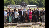People hold a minute of silence for prisoners assigned a pink triangle in the former Nazi concentration camp Buchenwald within the Christopher Street Day in Weimar, Germany, Sunday, June 23, 2019. There were 650 prisoners assigned a pink triangle in the Buchenwald concentration camp between 1937 and 1945. Many of them lost their lives. (AP Photo/Jens Meyer)
