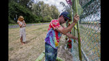 Brian Raley places large flowers and leaves as part of a memorial at the site where a Beechcraft King Air twin-engine plane crashed killing multiple people Friday evening near the chain link fence surrounding Dillingham Airfield, Saturday, June 22, 2019, in Mokuleia, Hawaii. At left, a good friend of Raley (she didn't want to give her name) and of the people who perished in the plane grieves for them. (Dennis Oda/Honolulu Star-Advertiser via AP)