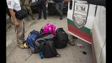 Bags belonging to migrants without legal permission to be in Mexico sit on the street next to an immigration van parked outside an Attorney General before migrants sitting inside the van are transported to Tapachula from Arriaga, Mexico, Sunday, June 23, 2019. Mexico has completed its deployment of 6,000 National Guard agents to help control the flow of migrants headed toward the U.S. and filled immigration agency posts to regulate border crossings, the government said Friday. (AP Photo/Oliver de Ros)