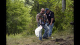 Motorcyclists recover personal items from the scene of a fatal accident on Route 2 in Randolph, N.H., Saturday, June 22, 2019. Investigators pleaded Saturday for members of the public to come forward with information that could help them determine why a pickup truck hauling a trailer collided with a group of motorcycles on a rural highway. (Paul Hayes/Caledonian-Record via AP)