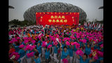 """FILE - In this Friday, July 31, 2015 file photo, participants celebrate following the announcement that Beijing will host the 2022 Winter Olympics at a gathering outside of the Beijing Olympic Stadium, also known as the Birds Nest, in Beijing. The sign reads """"Warm celebration of the successful Winter Olympics bid"""". Two candidates have stayed on the ballot to be held on Monday, June 24, 2019 to pick the 2026 Winter Olympics host. The IOC worked hard to help keep the Italian and Swedish candidates in the contest, giving both extra time to get their government's backing amid taxpayer concerns that Olympic hosting is an expensive luxury. Olympic officials hope the 2026 contest can shape a more efficient type of bidding and hosting. (AP Photo/Mark Schiefelbein, File)"""