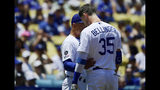 Los Angeles Dodgers manager Dave Roberts, left, talks with Cody Bellinger after Bellinger hit a fan with a foul ball during the first inning of a baseball game against the Colorado Rockies, Sunday, June 23, 2019, in Los Angeles. (AP Photo/Mark J. Terrill)