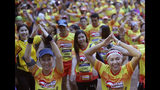 Runners warn up before the start of a marathon and biking event in Mae Sai, Chiang Rai province, Thailand, Sunday, June 23, 2019. Around 4,000 took part in the event Sunday morning, organized by local authorities to raise funds to improve conditions at the now famous Tham Luang cave complex. The youngsters went in to explore before rain-fed floodwaters pushed them deep inside the dark complex. Their rescue was hailed as nothing short of a miracle. (AP Photo/Sakchai Lalit)
