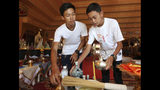 In this Saturday, June 22, 2019. members of the Wild Boars soccer team who were rescued from a flooded cave, Nattawut Takamrong, left, and Peerapat Sompiangjai volunteer at the Pratart Doiwao Temple in Mae Sai, Chiang Rai province, northern Thailand. Some of the 12 young Thai soccer players and their coach have marked the anniversary of their ordeal that saw them trapped in a flooded cave for two weeks with a commemorative marathon in northern Thailand. (AP Photo/Sakchai Lalit)