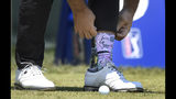Roberto Diaz pulls down his pant leg after tying his shoe at the first tee during the final round of the Travelers Championship golf tournament, Sunday, June 23, 2019, in Cromwell, Conn. (AP Photo/Jessica Hill)