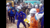 In this photo provided by Preah Sihanouk Provincial Authority, rescuers carry the body of a victim at the site of a building collapse, Monday, June 24, 2019, in Preah Sihanouk province, Cambodia. Rescuers on Monday continued to search the rubble of a building that collapsed while under construction in a Cambodian beach town, killing over two dozen workers and injuring 24 others as they slept in the unfinished condominium that was doubling as their housing. (Preah Sihanouk Provincial Authority via AP)