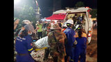 In this Sunday, June 23, 2019, photo provided by Preah Sihanouk provincial authorities, rescuers enter a victim body onto an ambulance at a site of a collapse in Preah Sihanouk province, Cambodia. Rescuers on Monday were continuing to search the rubble of a building that collapsed while under construction in a Cambodia beach town, killing dozens of workers as they slept in the unfinished condominium that was doubling as their housing. (Preah Sihanouk provincial authorities via AP)