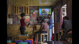 Ethiopians follow the news on television at a cafe in Addis Ababa, Ethiopia Sunday, June 23, 2019. Ethiopia's government foiled a coup attempt in a region north of the capital and the country's military chief was shot dead, the prime minister Abiy Ahmed said Sunday in a TV announcement. (AP Photo/Mulugeta Ayene)