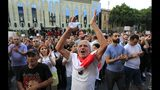 People applaud and listen to a speaker during a protest as opposition demonstrators gather in front of the Georgian Parliament building in Tbilisi, Georgia, Sunday, June 23, 2019. The protesters consider Georgia's current government to be overly cooperative with Russia. (AP Photo/Shakh Aivazov)