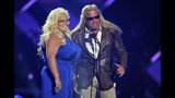 "FILE - In this Wednesday, June 5, 2013, file photo, Duane ""Dog"" Chapman, right, and Beth Chapman present the award for CMT performance of the year at the CMT Music Awards at Bridgestone Arena in Nashville, Tenn. Beth Chapman is in a medically induced coma in the intensive care unit of Queen's Medical Center in Honolulu, The Honolulu Star-Advertiser reported Sunday, June 23, 2019. Chapman was diagnosed with lung cancer in September 2017 and said in November 2018 that the cancer had returned despite surgery. (Photo by Donn Jones/Invision/AP, File)"