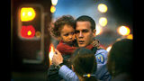 In this Nov. 17, 2003 photo, St. Louis Police officer Michael Langsdorf comforts a little girl who had just been dropped by her father from the third floor roof of a house after the house caught on fire in St. Louis. Langsdorf, a police officer responding to a bad check complaint at a food market, was shot and killed Sunday, June 23, 2019, near St. Louis. (J.B. Forbes/St. Louis Post-Dispatch via AP)