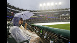 Kristin and Caleb Loosli wait out a rain delay during a baseball game between the Kansas City Royals and the Cleveland Indians, Monday, June 24, 2019, in Cleveland. (AP Photo/Tony Dejak)