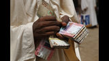 A money exchanger counts money at a popular market, in Khartoum, Sudan, Monday, June 24, 2019. Sudan's protest movement accepted an Ethiopian roadmap for a civilian-led transitional government, a spokesman said on Sunday, after a months-long standoff with the country's military rulers - who did not immediately commit to the plan. (AP Photo/Hussein Malla)