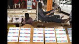 A street vendor who sells mobile sim card numbers, reads a newspaper at a popular market, in Khartoum, Sudan, Monday, June 24, 2019. (AP Photo/Hussein Malla)